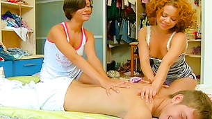 Two sensual chicks giving a massage to a half-naked chap