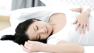 Likablely cute Asian poppet is posing on the bed without veil on her